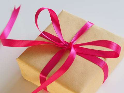 A present simply wrapped in plain brown gift paper is tied up neatly and prettily with a red ribbon
