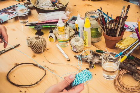 Hands are holding a white and blue twine, seemingly measuring it out to make something. They are on a light wood table covered in arts and crafts supplies: other twines, paintbrushes, beads, blues, feathers and more.