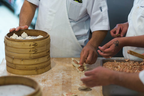 People learning to make a dish together, cooking dumplings.