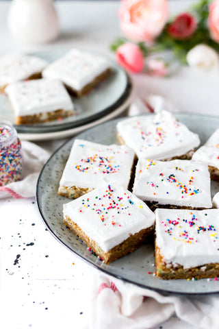 Cookie bar desserts are displayed on a neutral speckled plate. The treats have a thick layer of white icing and are decorated with rainbow sprinkles