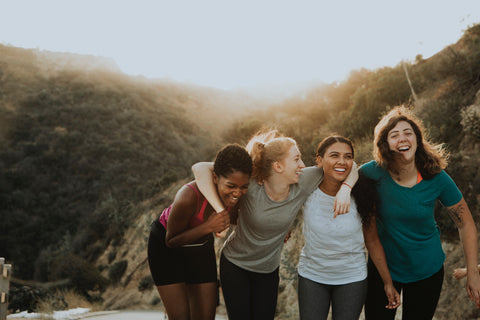 Four women are posed on a trail with their arms over their friends' shoulders, smiling and laughing.