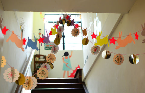paper streamers of various shapes, stars, flowers, circles, and rabbits, are strung across a hallway. they are colorful and beautiful. a painting of a little girl with an umbrella is seen in the background beneath a window. the artful touches, though simple, make the space feel special.