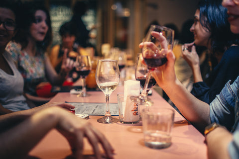 A large group of friends is sitting together at a table, eating and drinking while talking and laughing.