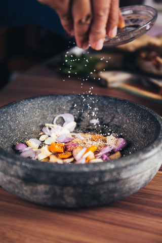 Someone is holding their hand over a bowl sprinkling salt into the bowl, which is filled with other spices, herbs, garlic and onion. The bowls is grey ceramic and sitting on a wood surface.