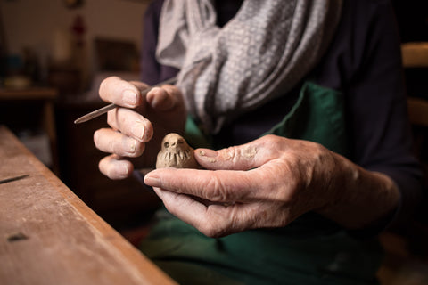 Two hands are holding a tiny clay bird that they are creating. There is clay on their hands and the tool they are using to add details, such as the eyes and the feathers around the neck, is gently pulled away while they decide on their next move.