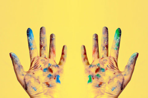 Two hands against a bright yellow background, the hands are covered in blue, green, and red paint.