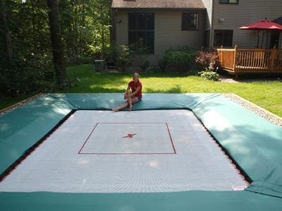 10x12 Ultimate Home Air Pro Trampoline installed in ground in a residential backyard with someone sitting on the side