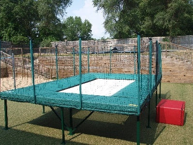 A MaxAir Above Ground Trampoline in a residential backyard with safety netting surrounding it