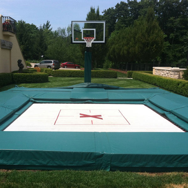 An in ground trampoline and a basketball hoop in a backyard