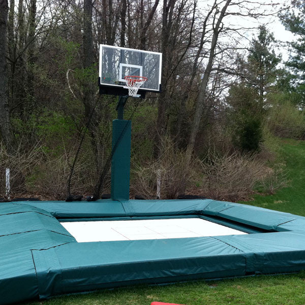 A MaxAir In Ground trampoline installed in a backyard next to a basketball hoop