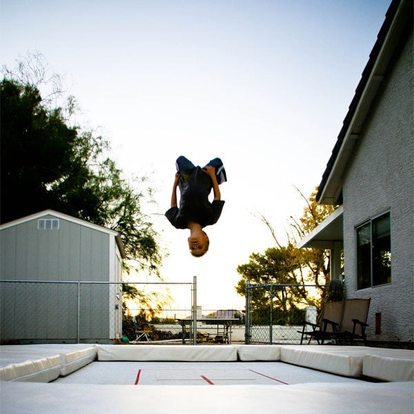A person doing a backflip on a backyard in ground trampoline at sunset