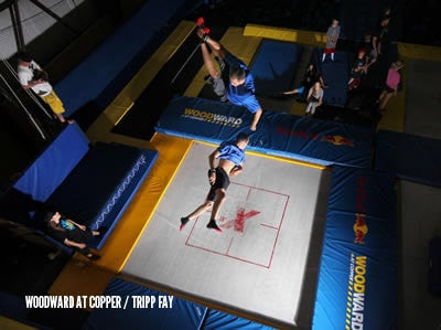 A Custom Trampoline in a bounce park with an athlete bouncing very high doing tricks