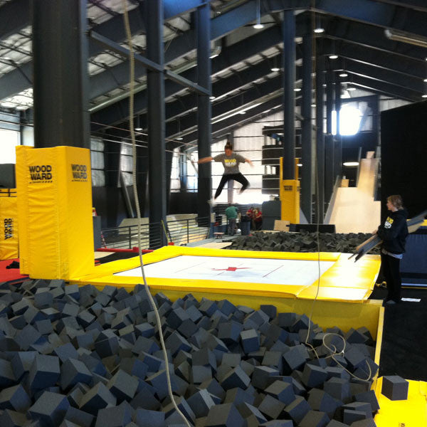 An indoor trampoline park with an athlete bouncing into a foam pit
