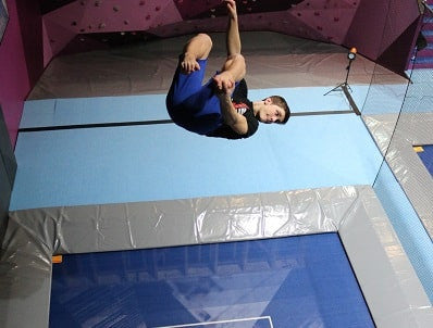 An athlete performing a backflip trick on a professional trampoline in a gymnastics facility