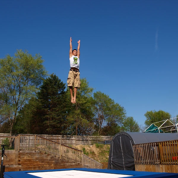 A person bouncing very high on a backyard trampoline