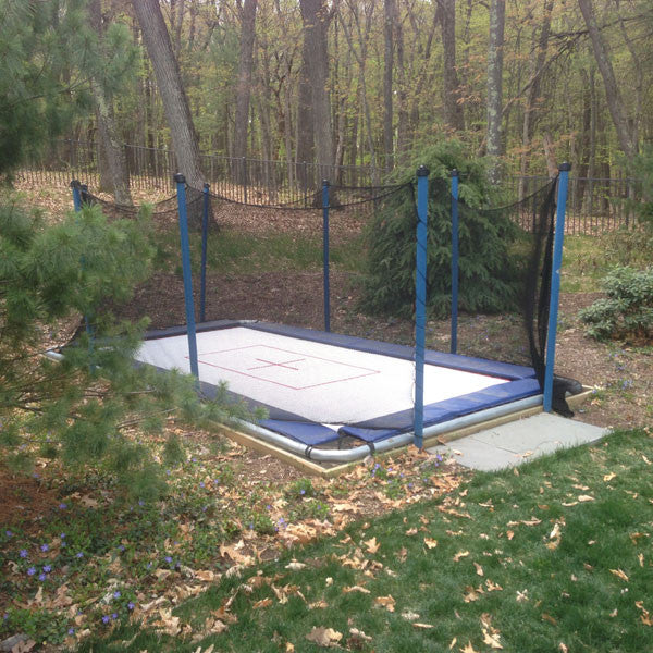 A built in trampoline with safety netting in a backyard