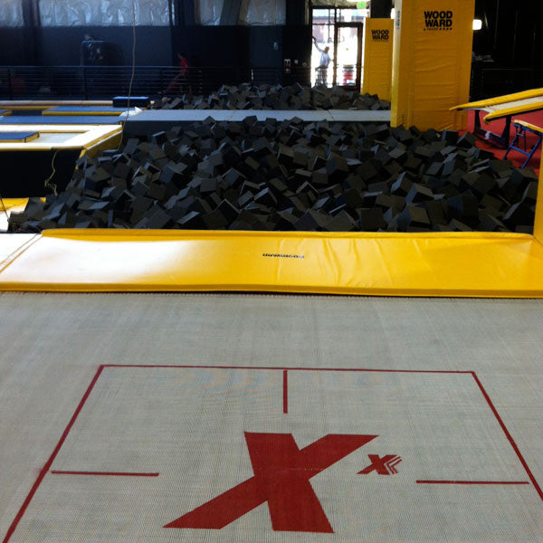 A MaxAir trampoline indoors next to a  foam pit