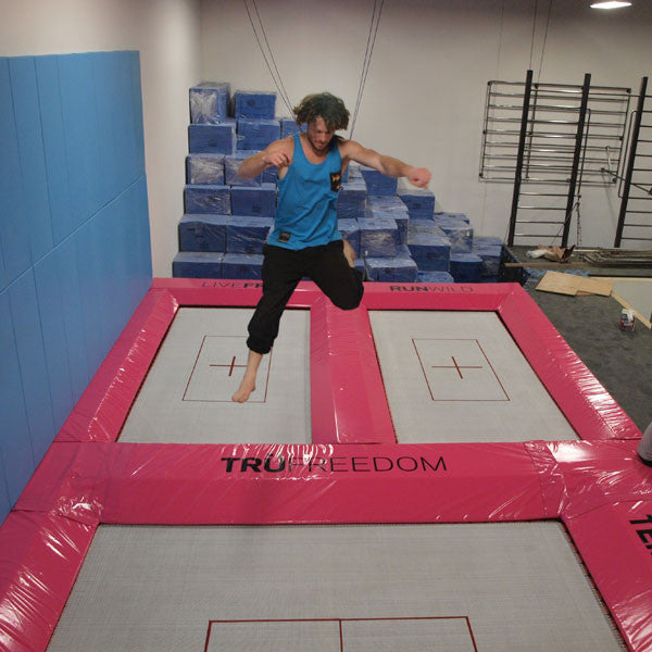 An athlete practicing tricks on a trampoline indoors