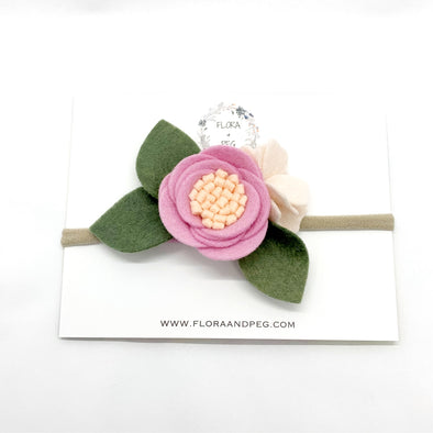 Purple-pink and peach felt flower headband with 3 green leaves.