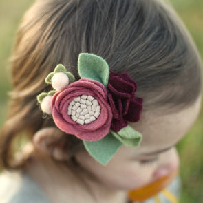 close up of toddler wearing dusty mauve felt flower clip.