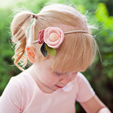 Close up of child wearing blush pink felt flower headband
