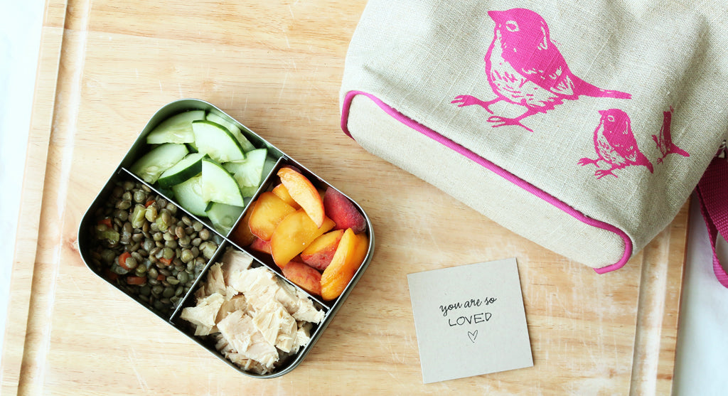 kids lunchbox with healthy food and pink bird lunchbag