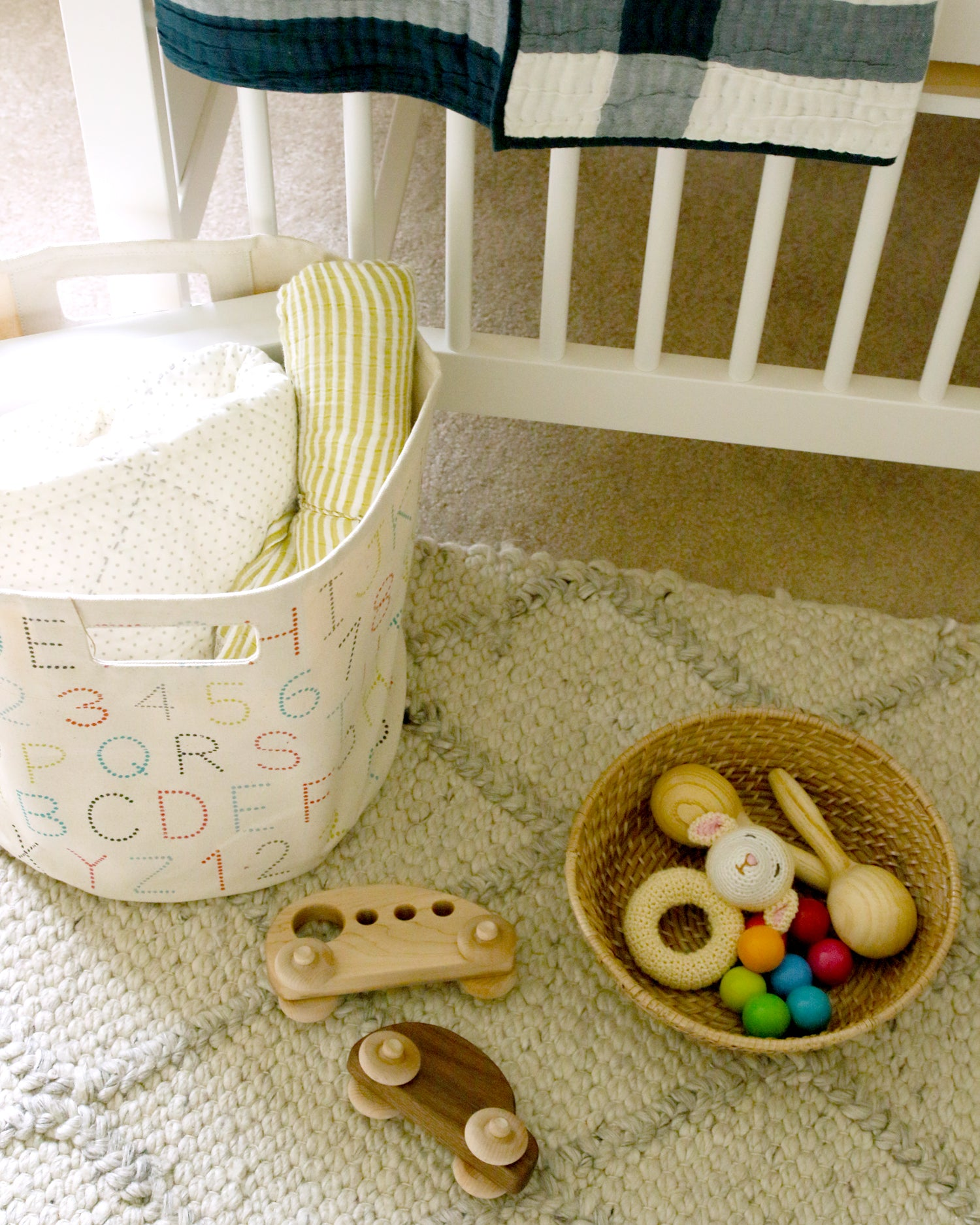 wood car and rattles in baby boy nursery