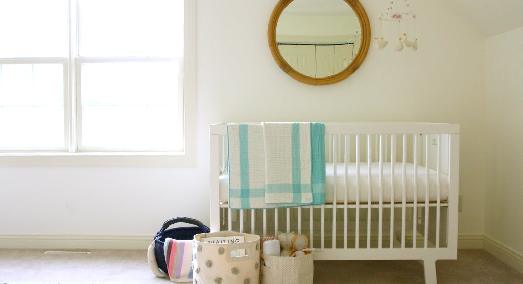 bright girl's nursery with crib and colorful quilt