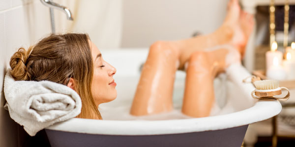 Woman enjoying a relaxing bath while practicing a self-care routine
