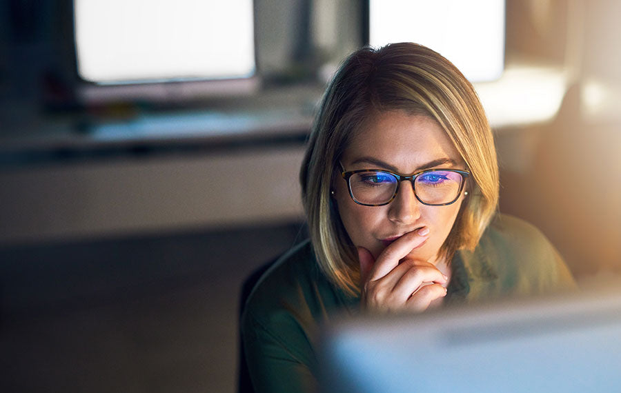 A woman looking at her computer screen with the blue light reflection in her glasses