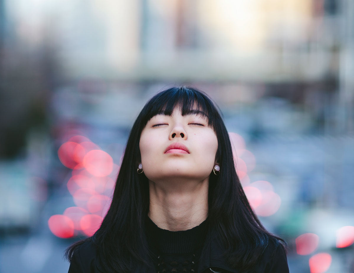 Face of a woman with her eyes closed pointed towards the sky in the city