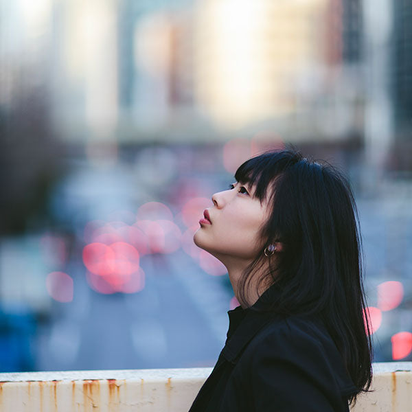 Side profile of a woman's face looking up at the sky in the city