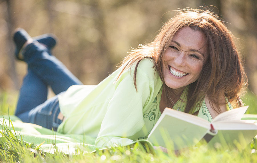 A woman laying in the grass and reading a book in the sunlight