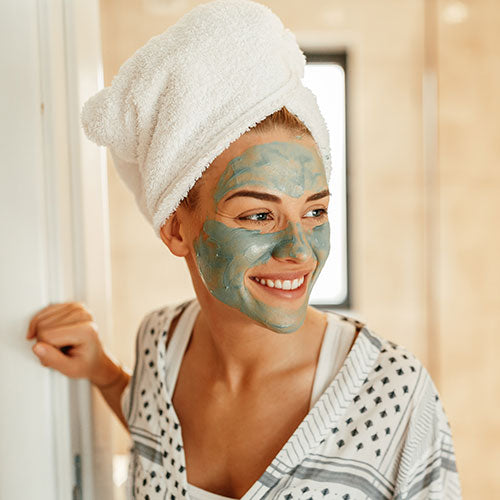 A woman in a face mask smiling