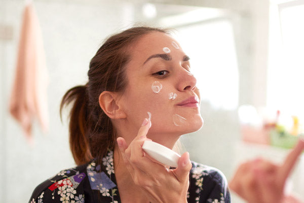 A woman applying skincare product to the face
