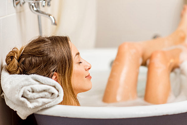 A woman lounging in the bath tub