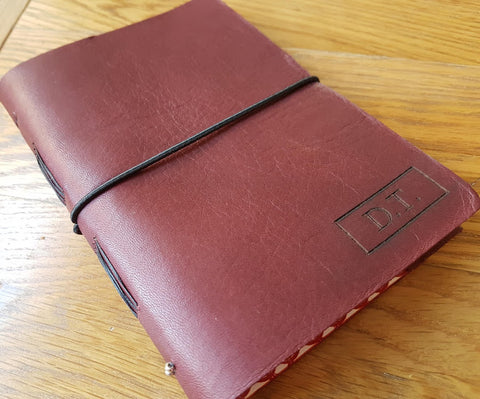 Moleskine style leather travel journal in burgundy leather showing elastic loop fastening