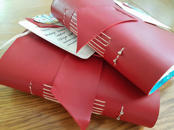 Red Leather bound travel journals with beaded spine by bespoke bindery