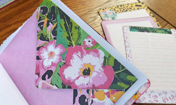 large floral design on flap of journaling envelop and matching cards in the background