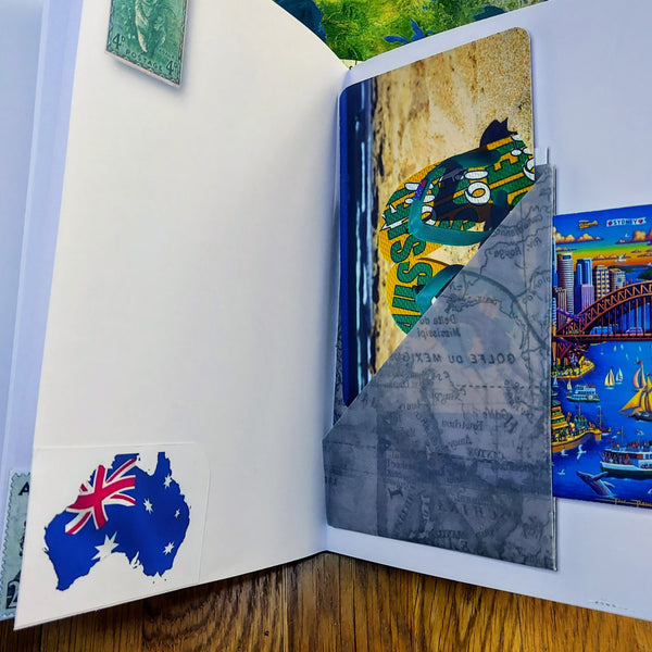 Open pages in Australia themed journal with multi-pocket and journaling cards.  opposite page with koala stamp and Australia Flag as a map