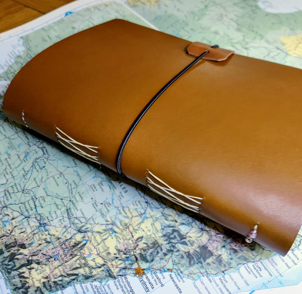 Australian theme A5 leather travel journal sitting on open Atlas map of Australia