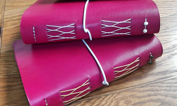 Two cerise pink leather journals with french link stitch binding and glass beads