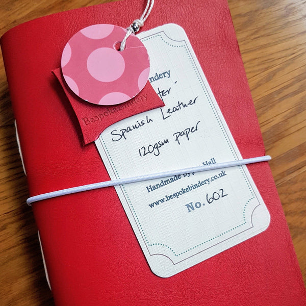 red Leather Golfing journal for ladies with white elastic closure and hand written tag