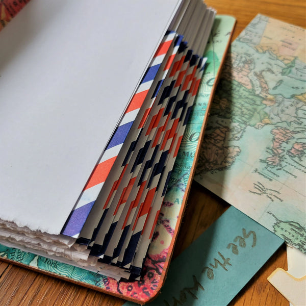 airmail envelopes equally spaced in the travel journal notebook forming envelope pockets to store travel related items