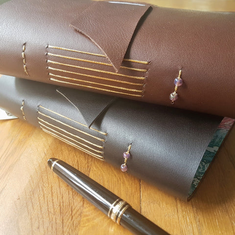 2 leather travel journals in chocolate and dark brown showing hand stitching and glass beads on spine