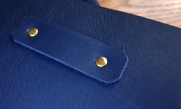 gold coloured fixings on closure loop on front of navy leather memoire journal
