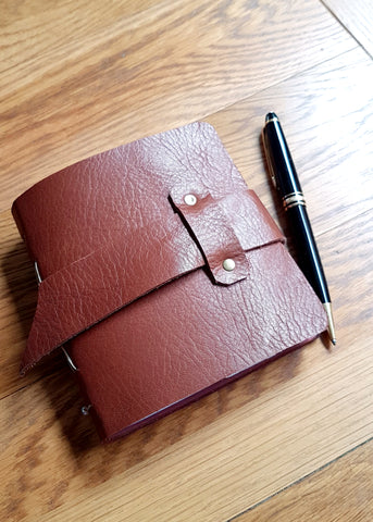 brown leather journal with graphic papers and pockets, showing front view with fixed loop for leather strap