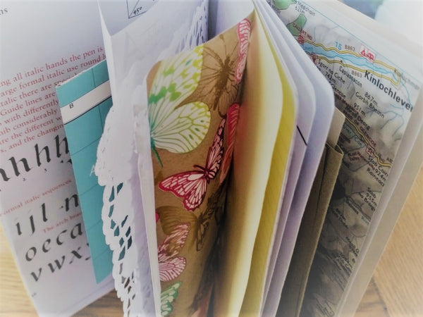 Mixed paper pages include calligraphy, lace doily, maps and other journaling and scrapbooking items