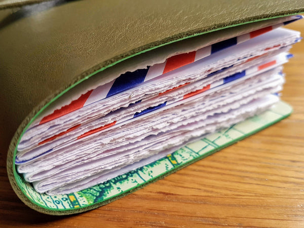 olive or moss green travel journal with airmail envelope pockets end view with deckled edes to thick white paper