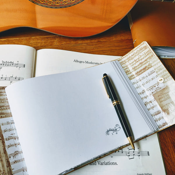 open music composintion book with blank forst page ready for inscription, guitar in background and mont blanc pen